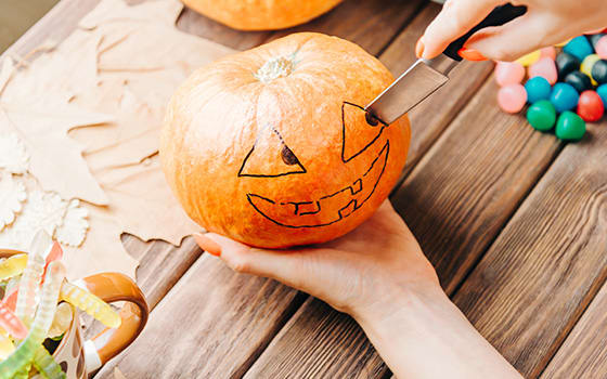 View_of_female_hands_carve_with_knife_a_pumpkin_for_Halloween_holiday.jpg